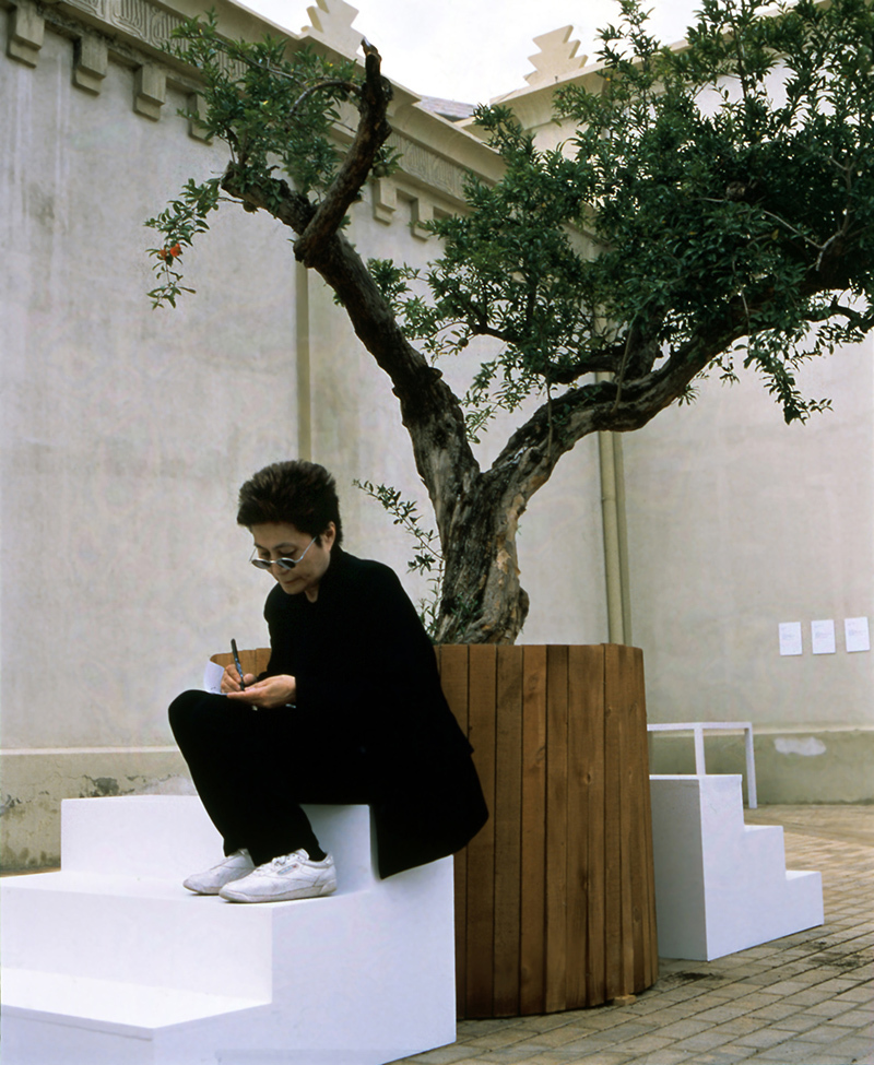 """Yoko Ono, """"Wish Tree,"""" 1996/1997, Installation view with artist seated, En Trance – Ex It, Lonja del Pescado, Alicante, Spain (June 23 – July 25, 1997), Photo: Miguel Angel Valero, Courtesy of Yoko Ono"""